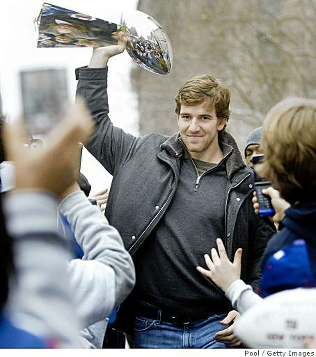NEW YORK - FEBRUARY 5: New York Giants quarterback Eli Manning makes his way to the stage carrying the Vince Lomardi Trophy for a ceremony honoring the team February 5, 2008 in New York City. The Giants beat the New England Patriots in Super Bowl XLII 17-14 on Sunday. (Photo by Julie Jacobson-Pool/Getty Images)