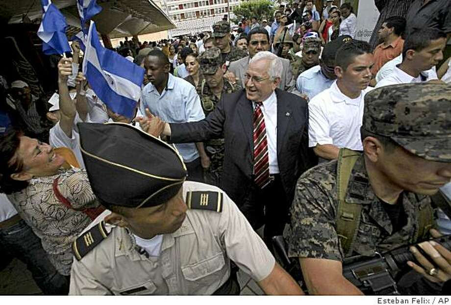 Honduras' congressional leader Roberto Micheletti,  whom Congress appointed president on Sunday, leaves escorted by soldiers a rally against ousted President Manuel Zelaya at the central park in Tegucigalpa, Tuesday June 30, 2009. The U.N. General Assembly demanded the immediate restoration of ousted president Zelaya but Micheletti said Zelaya could be arrested if he returns home.(AP Photo/Esteban Felix) Photo: Esteban Felix, AP