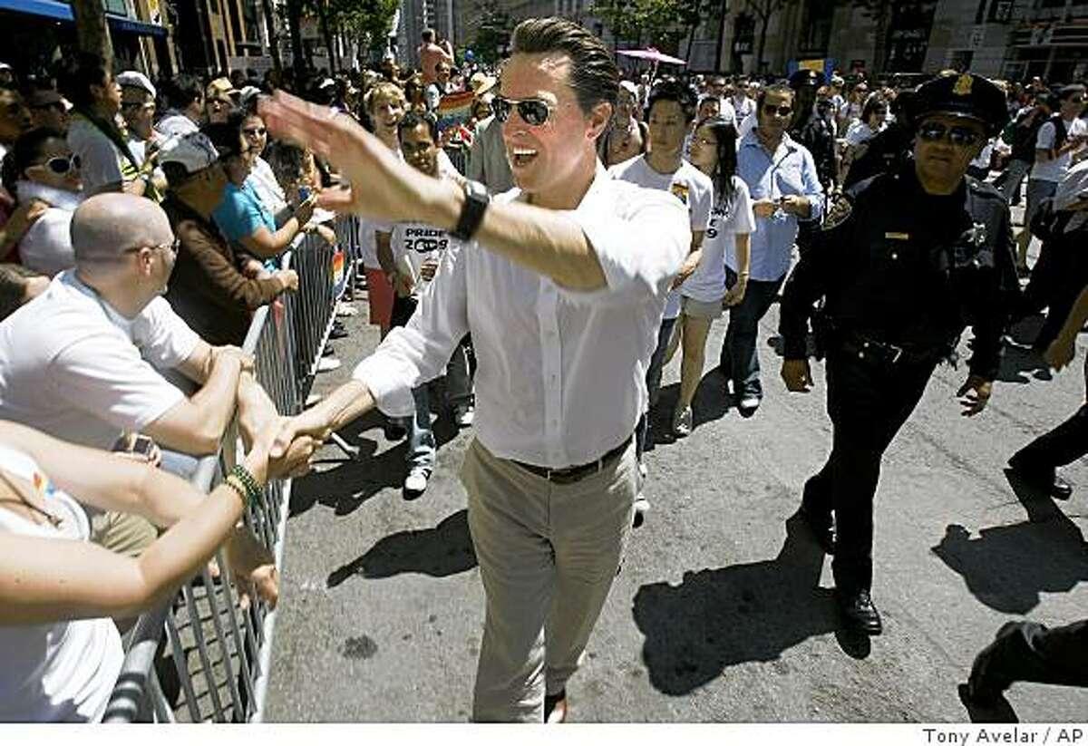 San Francisco Mayor Gavin Newsom greets spectators at the Gay Pride Parade on Sunday.