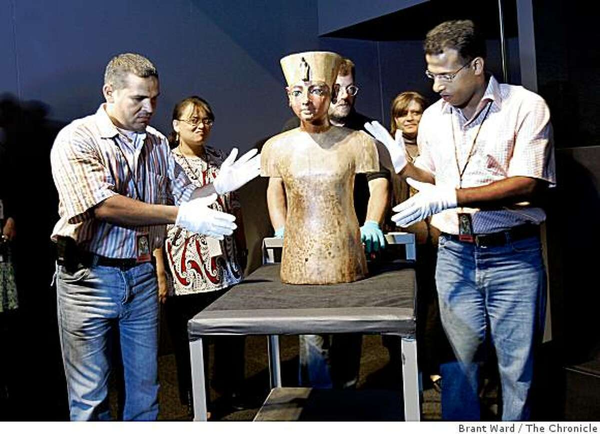 Mr. Samih (left) and Mr. Kamal from Egypt wore gloves as they wheeled the wooden bust into the display area. Conservators from Alexandria, Egypt brought a wooden bust of King Tutankhamun into the de Young museum Tuesday June 16, 2009 for a media preview of the upcoming exhibit.