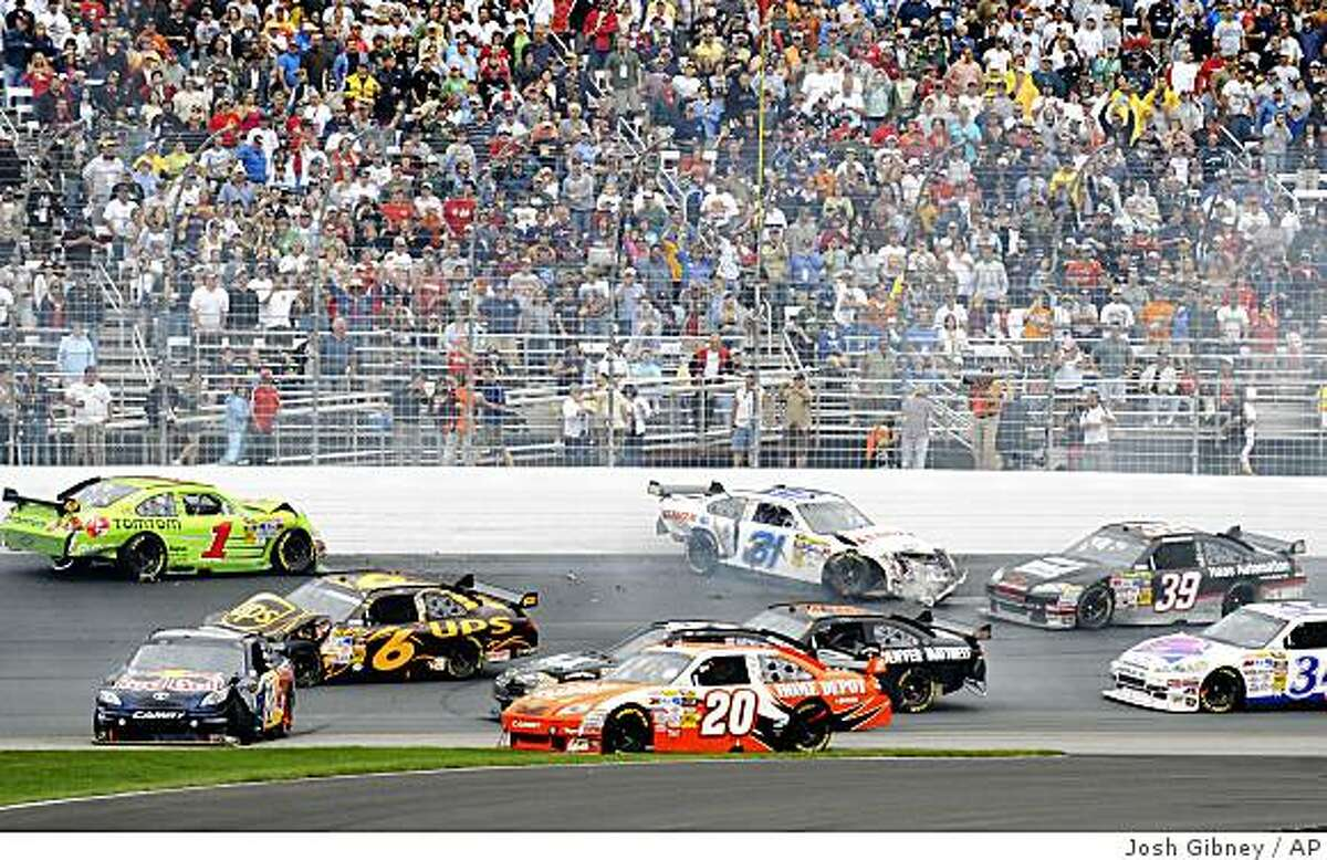 Joey Logano (20) makes it past a crash during the NASCAR Lenox Industrial Tools 301 auto race at New Hampshire Motor Speedway in Loudon, N.H., Sunday, June 28, 2009. Logano went on to win the rain-shortened race. (AP Photo/Josh Gibney)