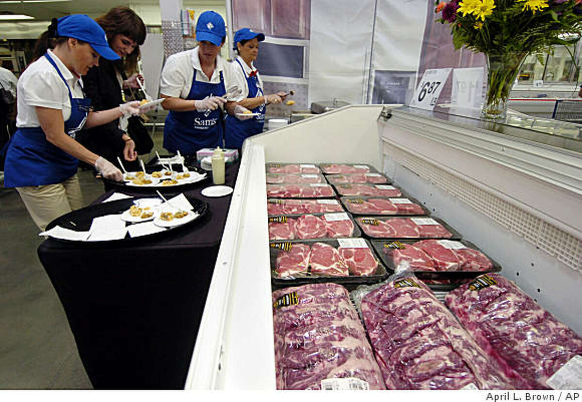 In this photo made Thursday, June 4, 2009, Sam's Club associates ready samples in front of a case of Angus beef at a Sam's Club in Bentonville, Ark. Sam's Club parent company Wal-Mart Stores Inc. is upgrading its beef, clothing, electronics and home accessories while sprucing up its stores as it maneuvers to retain these spenders who have embraced a newfound thriftiness. (AP Photo/April L. Brown)