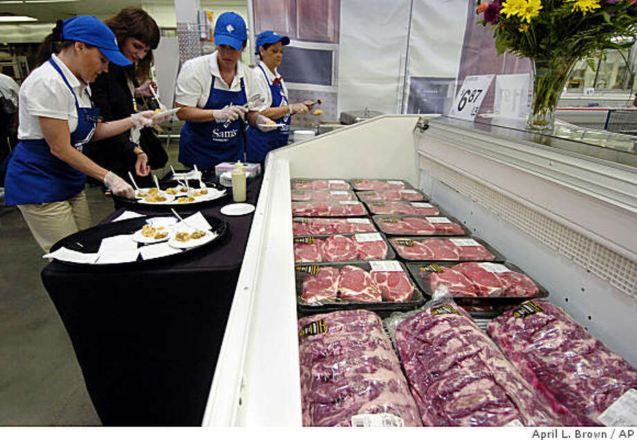 In this photo made Thursday, June 4, 2009, Sam's Club associates ready samples in front of a case of Angus beef at a Sam's Club in Bentonville, Ark. Sam's Club parent company Wal-Mart Stores Inc. is upgrading its beef, clothing, electronics and home accessories while sprucing up its stores as it maneuvers to retain these spenders who have embraced a newfound thriftiness. (AP Photo/April L. Brown) Photo: April L. Brown, AP