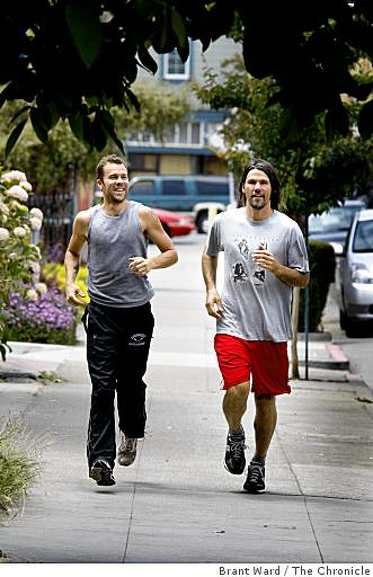 Brian (left) and Matt (right) run down 49th Street near Telegraph Avenue. Matt Szymankowski and Brian Rutherford are running from Oakland to Portland, 831 miles, to raise money for several causes.