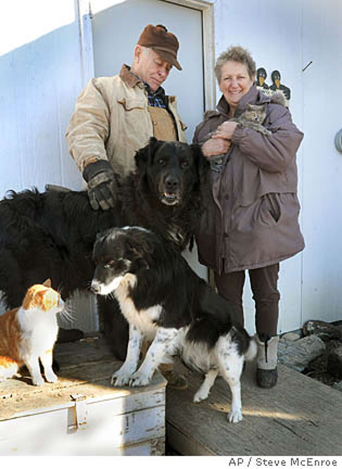 **ADVANCE FOR SUNDAY, FEB. 10** Al and Margaret Falzerano are surrounded by the family dogs Tippy and Buster, who sniffs at one of the many family cats, on their front porch of their rural Newell, SD ranch home on Thursday, Jan. 31, 2008. The couple met and married within two weeks after meeting through a rural matchmaking service. (AP Photo/Steve McEnroe)