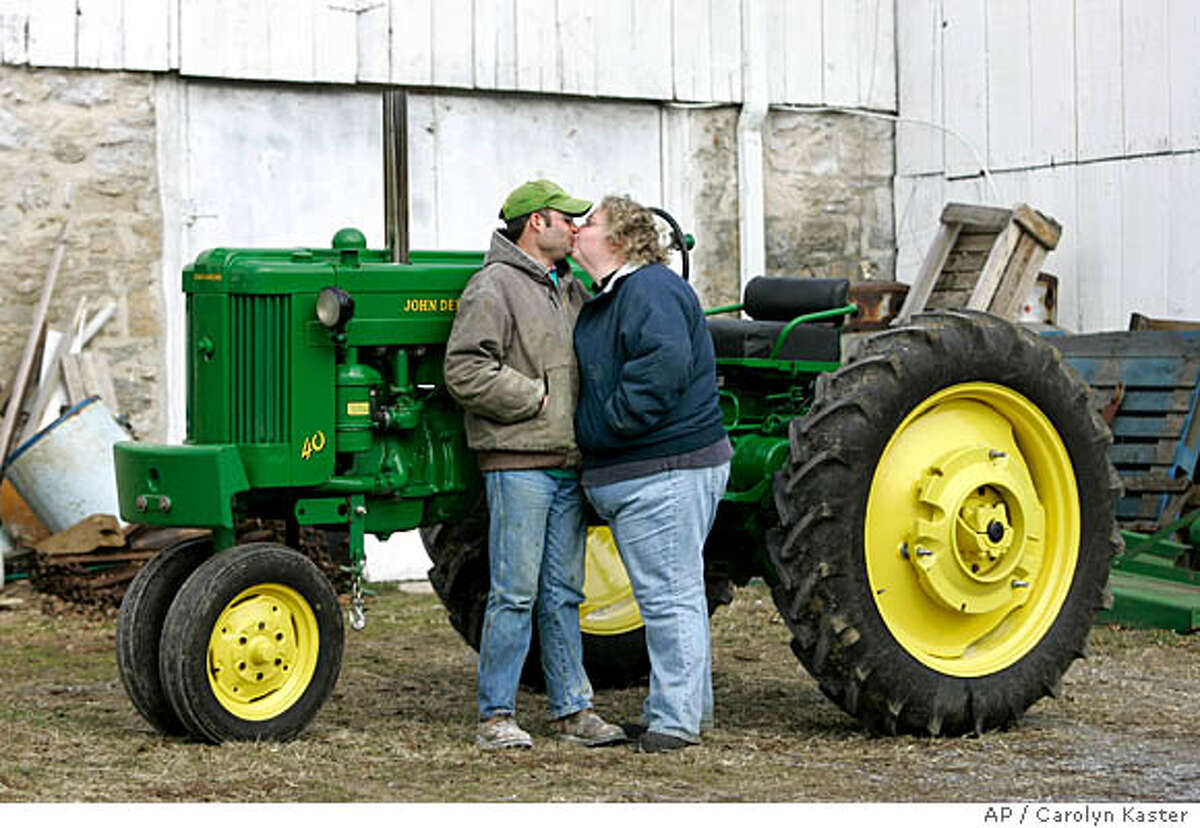 **ADVANCE FOR SUNDAY, FEB. 10** Tom Henisee, left, and his fiancee Sonya Rinker are photographed with Tom's antique John Deere 40 from 1955 at Tom home in Mount Joy, Pa., Saturday, Jan 26, 2008. The couple met using an Internet rural matchmaking service and are now planning an August wedding. (AP Photo/Carolyn Kaster)