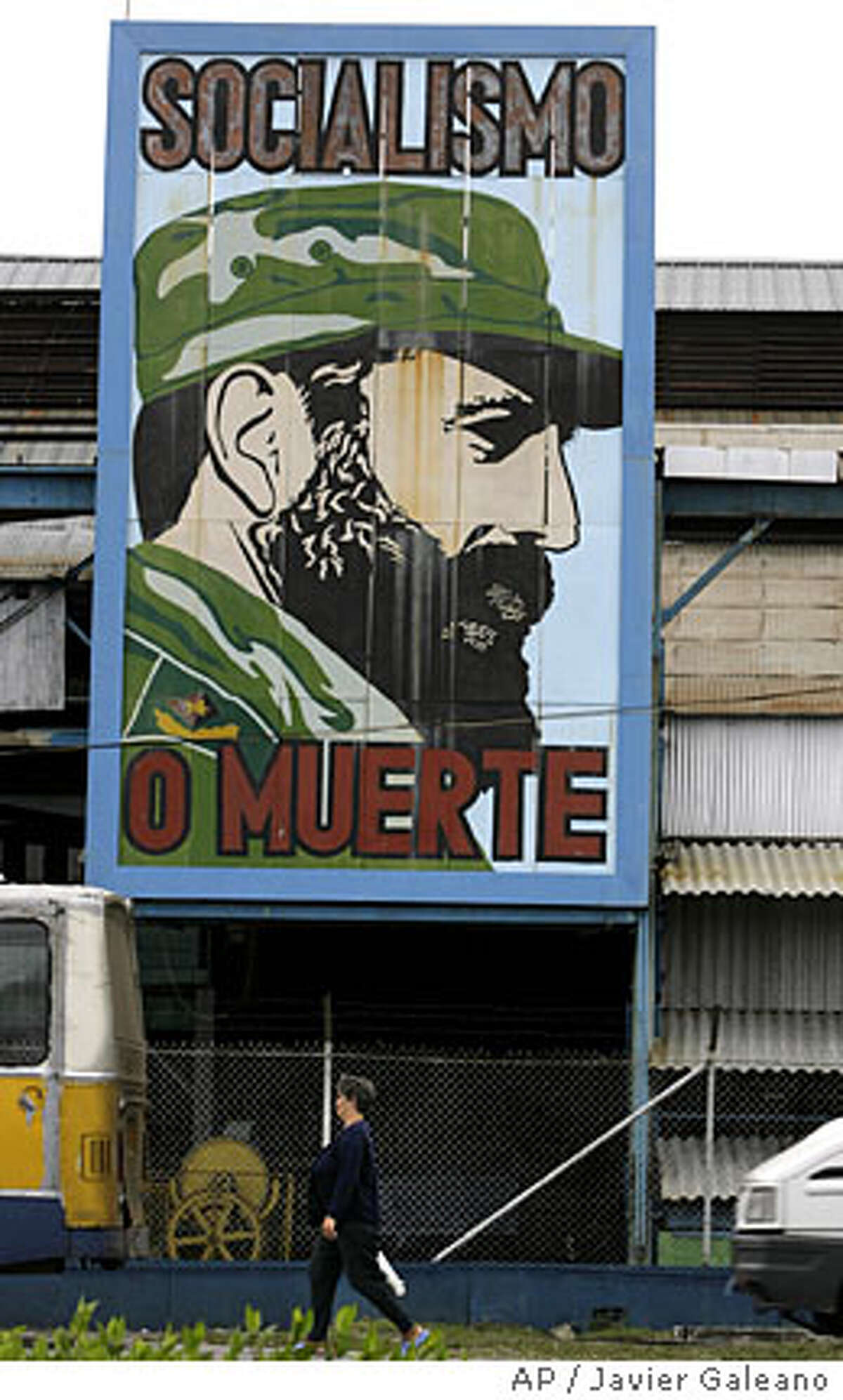 A woman walks past a billboard showing Cuban leader Fidel Castro with the words reading in Spanish 'Socialism or death', in Havana, Tuesday, Feb.19, 2008.Ailing leader Fidel Castro resigned as Cuba's president early Tuesday after nearly a half-century in power, saying he will not accept a new term when the newly elected parliament meets on Sunday.(AP Photo/Javier Galeano)