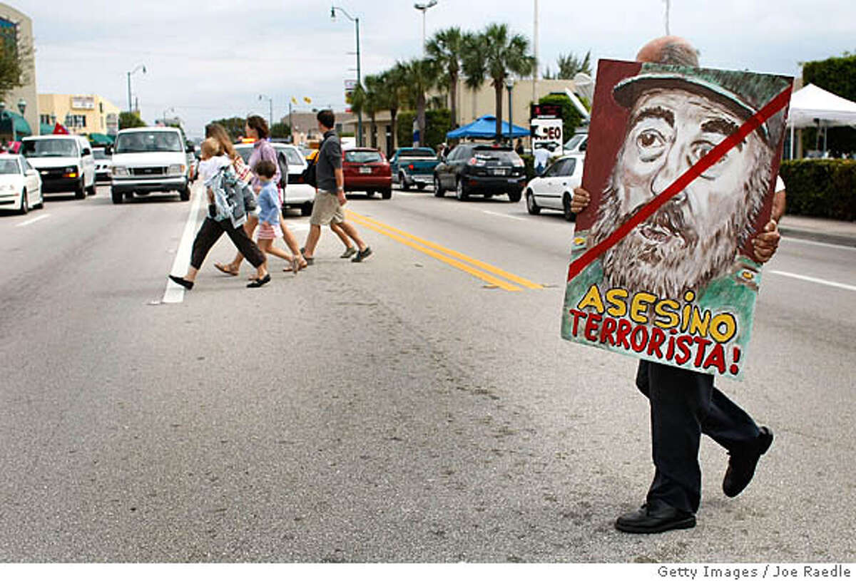 MIAMI - FEBRUARY 19: Alfredo Rey crosses the street holding a painting of Cuban President Fidel Castro that reads,