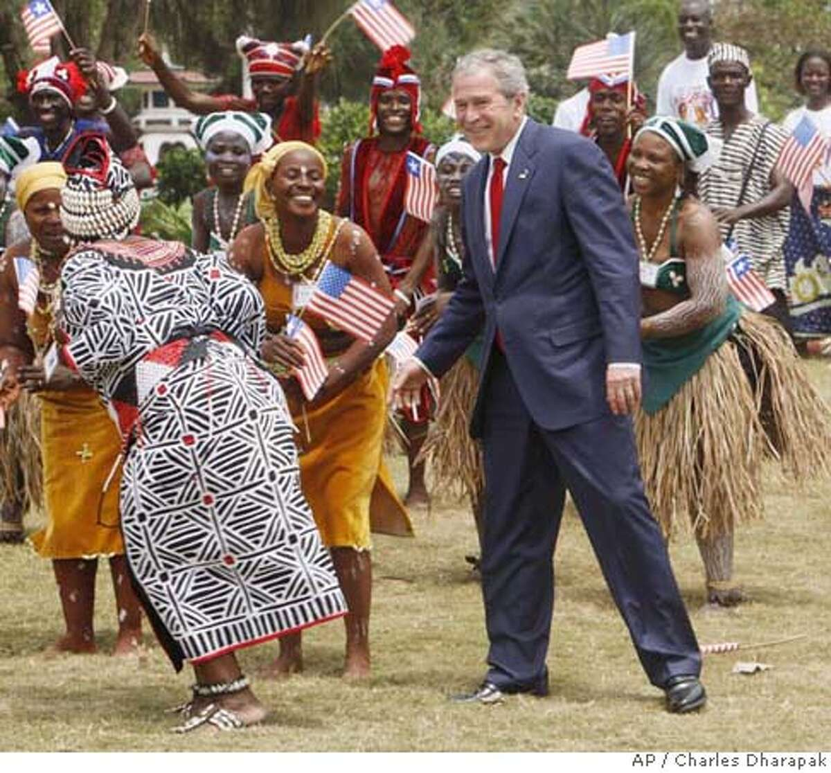 President Bush is pictured with traditional Liberian dancers before a lunch, Thursday, Feb. 21, 2008, in Monrovia, Liberia. (AP Photo/Charles Dharapak)