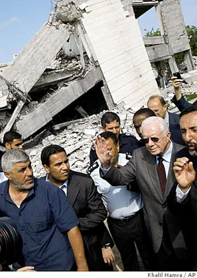 Former US President Jimmy Carter, right, waves to the media as he stands at the ruins of the American International School, which was destroyed during Israel's offensive in Gaza earlier this year, in Beit Lahiya, northern Gaza Strip, Tuesday, June 16, 2009. Carter says he's trying to persuade Hamas leaders to accept the international community's conditions for ending its boycott of the Islamic militant group. (AP Photo/Khalil Hamra) Photo: Khalil Hamra, AP