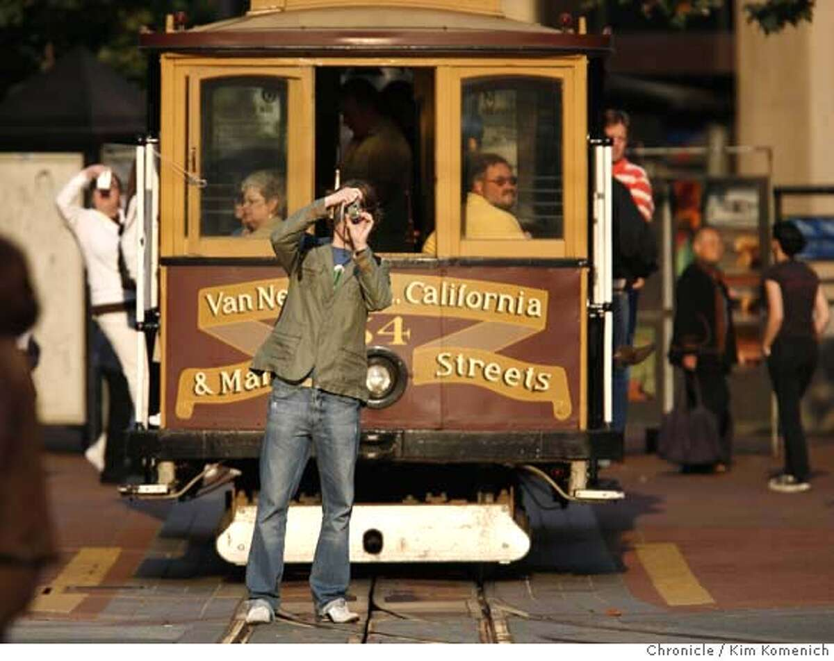 Cable car riders photograph the California Street tracks from Drumm Street in downtown San Francisco on Sunday, Sept. 30, 2007. Tourism is San Francisco's leading industry, generating $7.3 billion in 2006. Photo by Kim Komenich/San Francisco Chronicle MANDATORY CREDIT FOR PHOTOG AND SAN FRANCISCO CHRONICLE. NO SALES- MAGS OUT.
