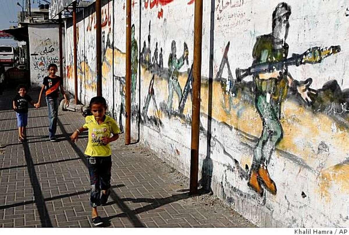 Palestinian girls walk past a graffiti-decorated wall depicting masked and armed Hamas militants, in Jabaliya, northern Gaza Strip, Monday, June 15, 2009.