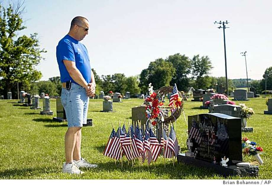 ** ADVANCE FOR SUNDAY, JULY 28 **In this May 18, 2009  photo, Steve Moore remembers his brother, David, at his grave in Dubois, Ind. Sgt. David Moore died last year of a lung disorder after serving in the National Guard in Iraq where his brother believes he was exposed to a deadly chemical. (AP Photo/Brian Bohannon) Photo: Brian Bohannon, AP