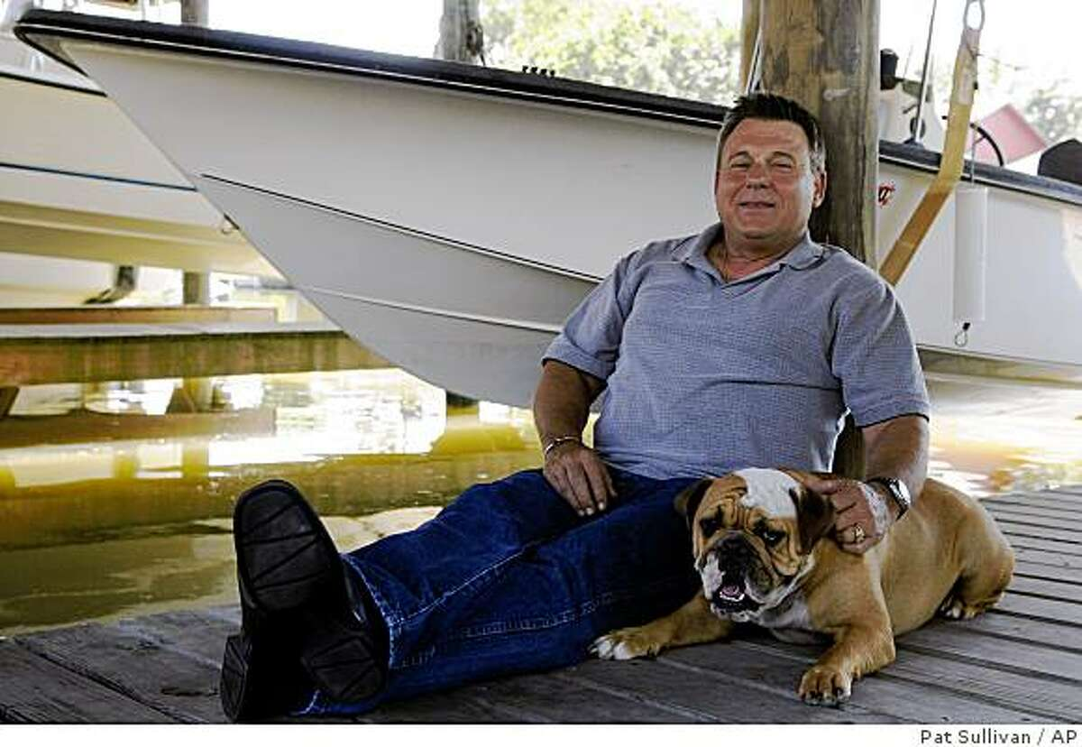** ADVANCE FOR SUNDAY, JULY 28 **In this , May 19, 2009 photo, former KBR employee Danny Langford relaxes with bulldog, Deuce, on his son's deck in Texas City, Texas. Langford said that after exposure to a chemical used by KRB in Iraq,