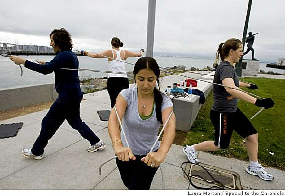 Goli Shariat (center) works on a strength exercise with others during a fitness class organized by BootCampSF outside at China Basin in San Francisco, Calif., on Friday, June 12, 2009. Photo: Laura Morton, Special To The Chronicle