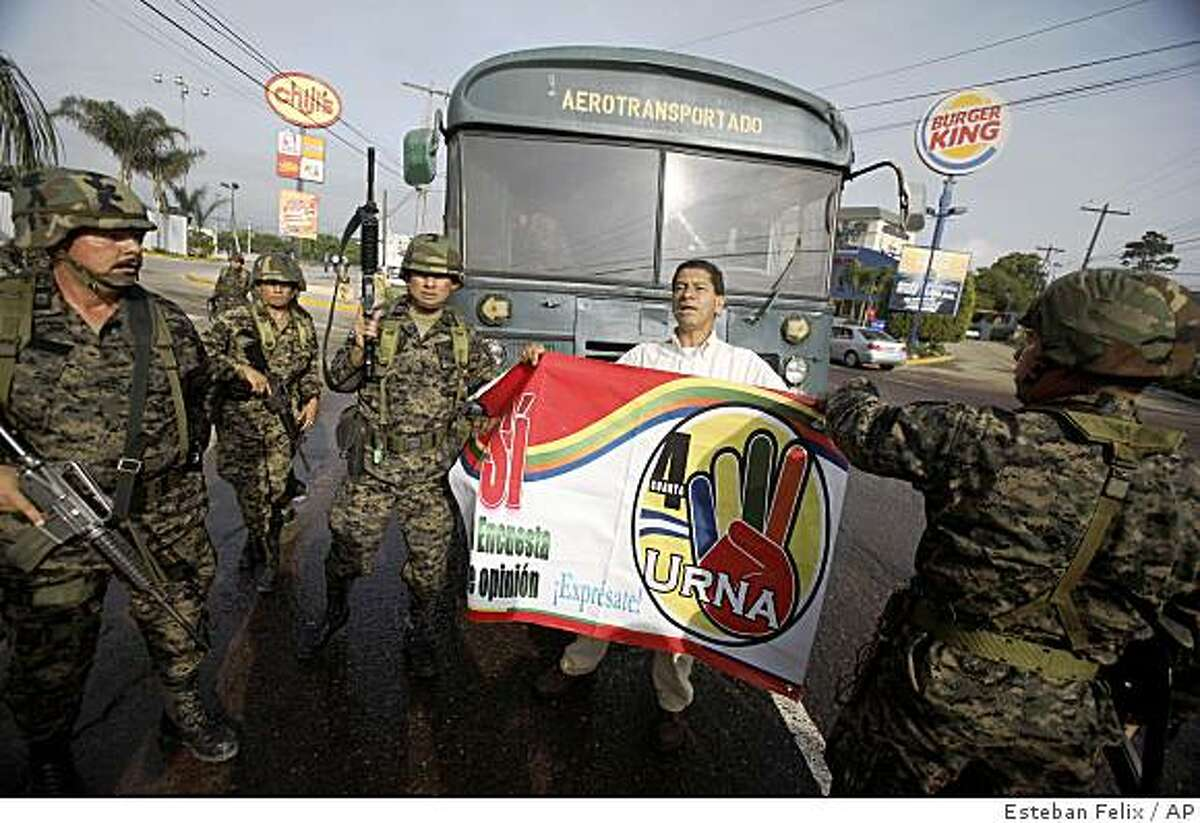 Soldiers try to stop a supporter of Honduras' President Manuel Zelaya from holding up a banner that reads in Spanish