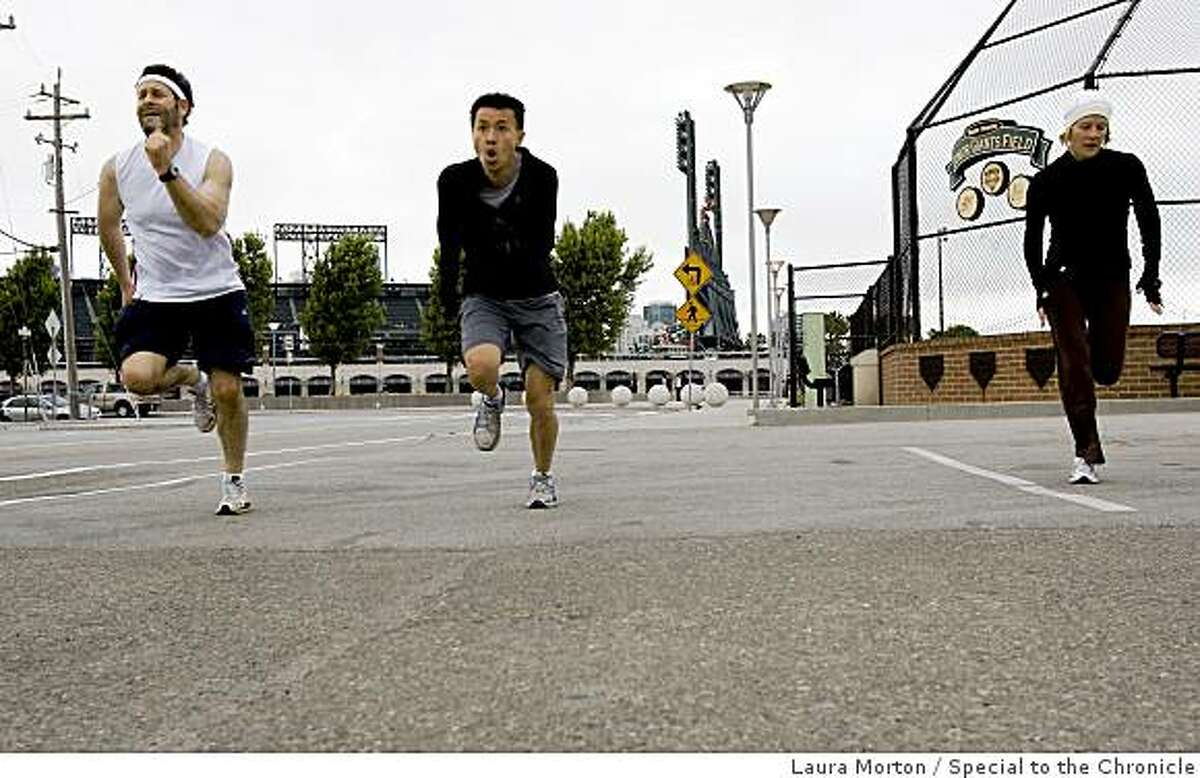 Richard Shapiro, Paul Chan and Amy Strickland (left to right) run sprints while participating in a fitness class organized by BootCampSF outside at China Basin in San Francisco, Calif., on Friday, June 12, 2009.