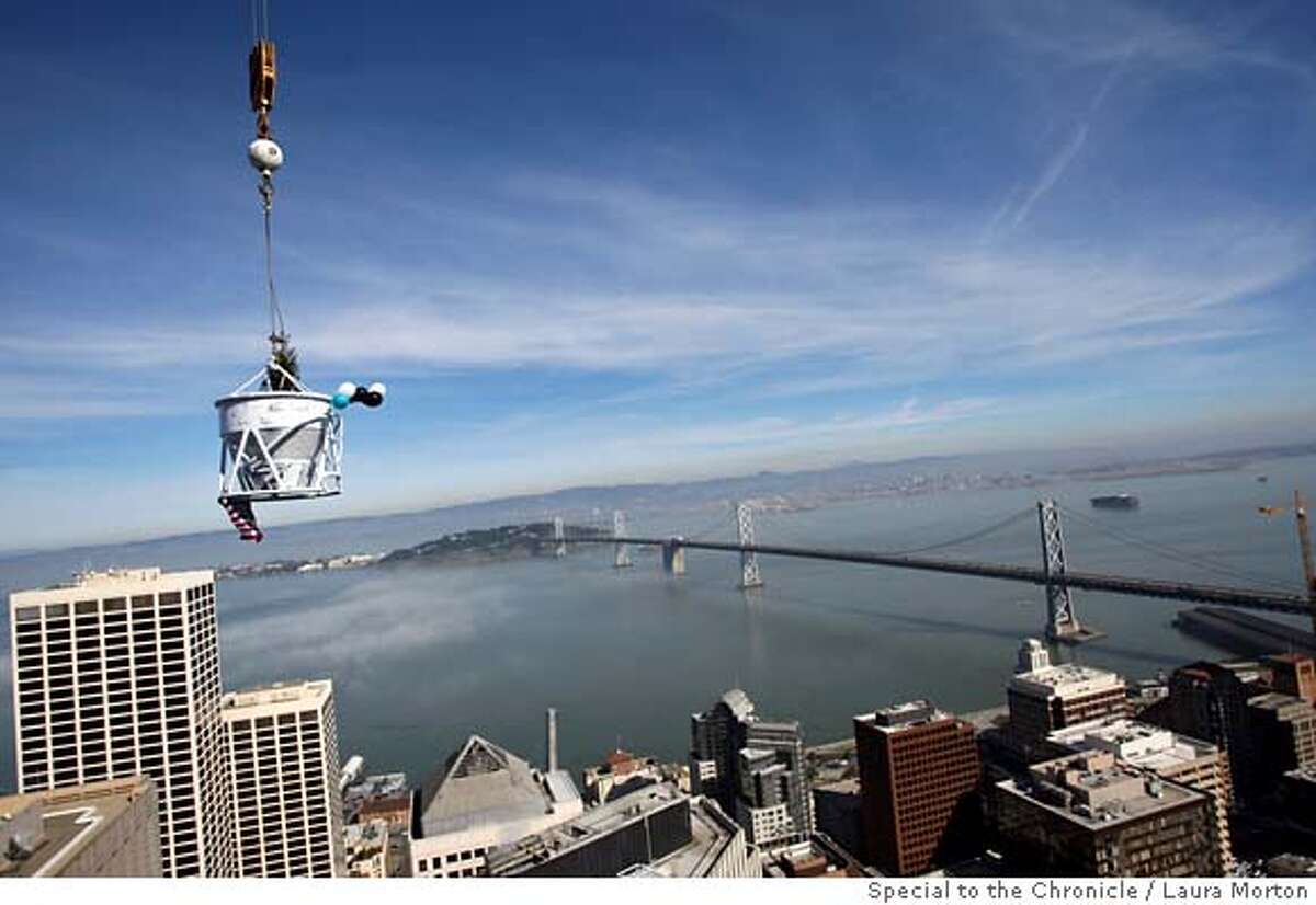 A concrete bucket with a ceremonial tree inside is raised above the San Francisco skyline on it's way to the top of Millennium Tower, the 60-story luxury residential tower at Mission between Fremont and Beale streets, during a ceremonial