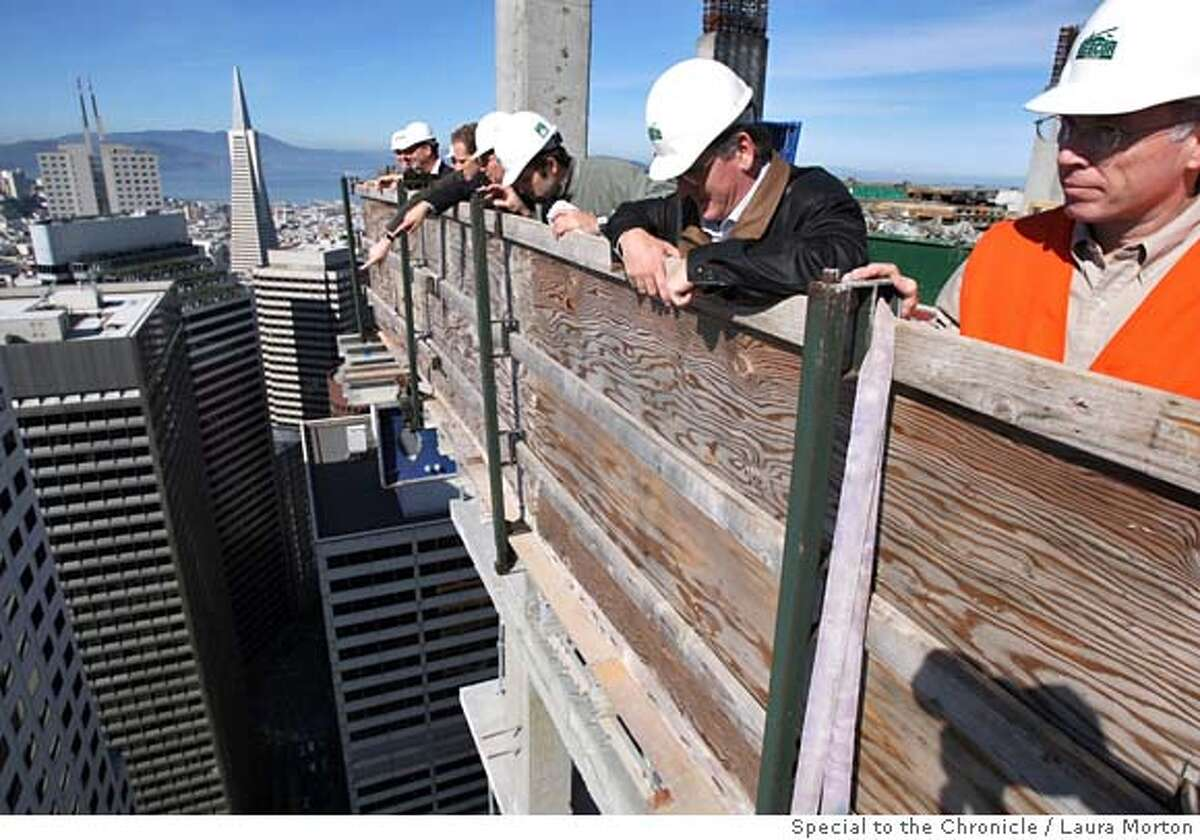 Bob Kane (right) looks over edge of the roof of Millennium Tower with others from Webcor during a ceremonial