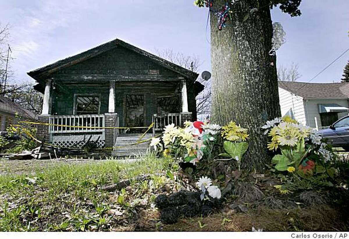 ** ADVANCE FOR SUNDAY, JUNE 21** In this May 14, 2009 photo, synthetic flowers at the base of a tree form a temporary memorial to Gordon Yoesting in front of the burned home where he died last October on 1430 Jane Ave. in Flint, Mich. (AP Photo/Carlos Osorio)