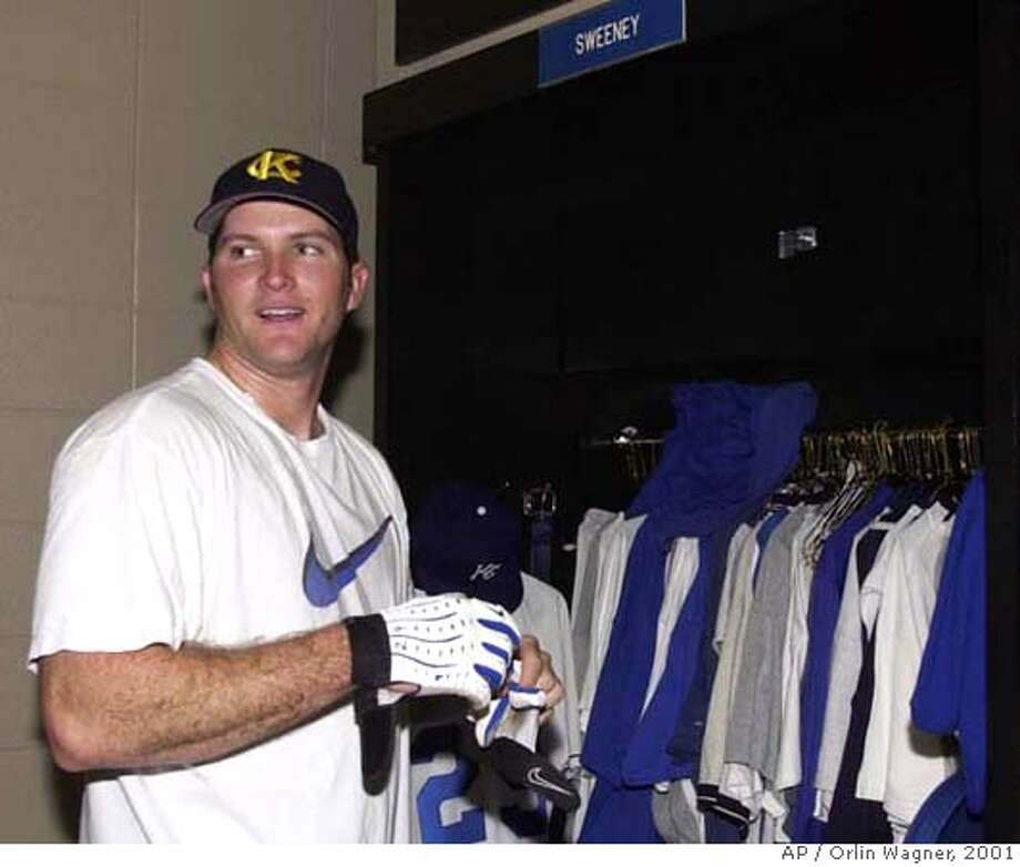 Kansas City Royals first baseman Mike Sweeney takes off batting gloves next to his locker following a workout at Kauffman Stadium, Thursday, Jan. 18, 2001, in Kansas City, Mo. The Royals avoided arbitration with the All-Star first baseman Thursday by signing Sweeney to a two year deal. (AP Photo/Orlin Wagner) DIGITAL IMAGE Photo: ORLIN WAGNER