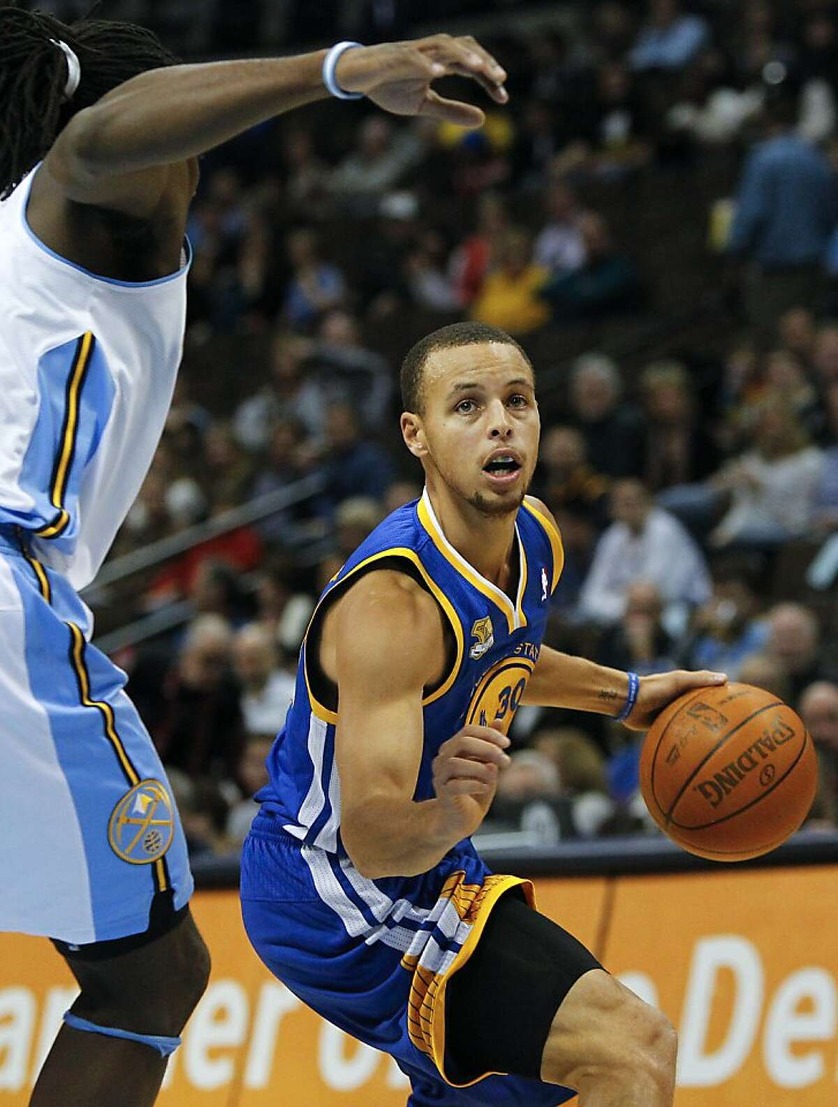 Golden State Warriors guard Stephen Curry (30) drives past Denver Nuggets forward Kenneth Faried (35) during the first quarter of an NBA basketball game Thursday, Feb. 9, 2012, in Denver. (AP Photo/Barry Gutierrez)