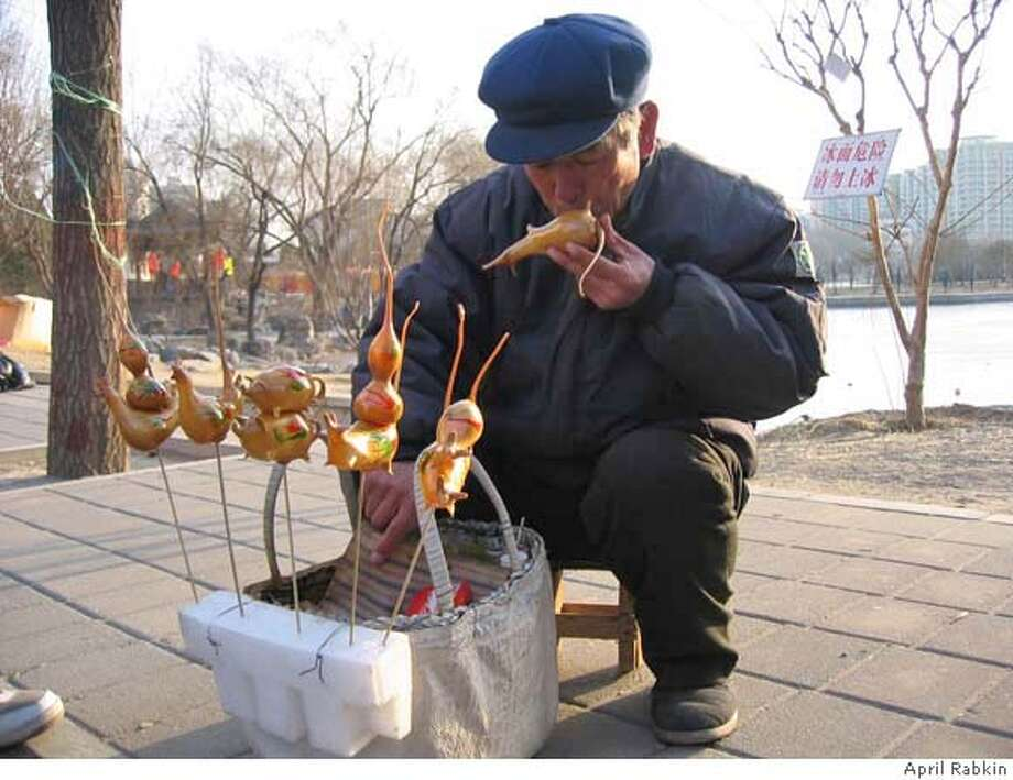 Song Cheng Dong blows up rat balloons made of taffy for the  Chinese New Year. He learned how make them from his father, who  learned from his grandfather.  photo: April Rabkin Photo: April Rabkin
