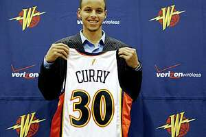 Golden State Warriors top draft pick Stephen Curry poses with his new jersey during a news conference at the Warriors headquarters in Oakland, Calif., Friday, June 26, 2009. Curry, a guard from Davidson College, was selected No. 7 overall in the basketball draft. (AP Photo/Paul Sakuma)