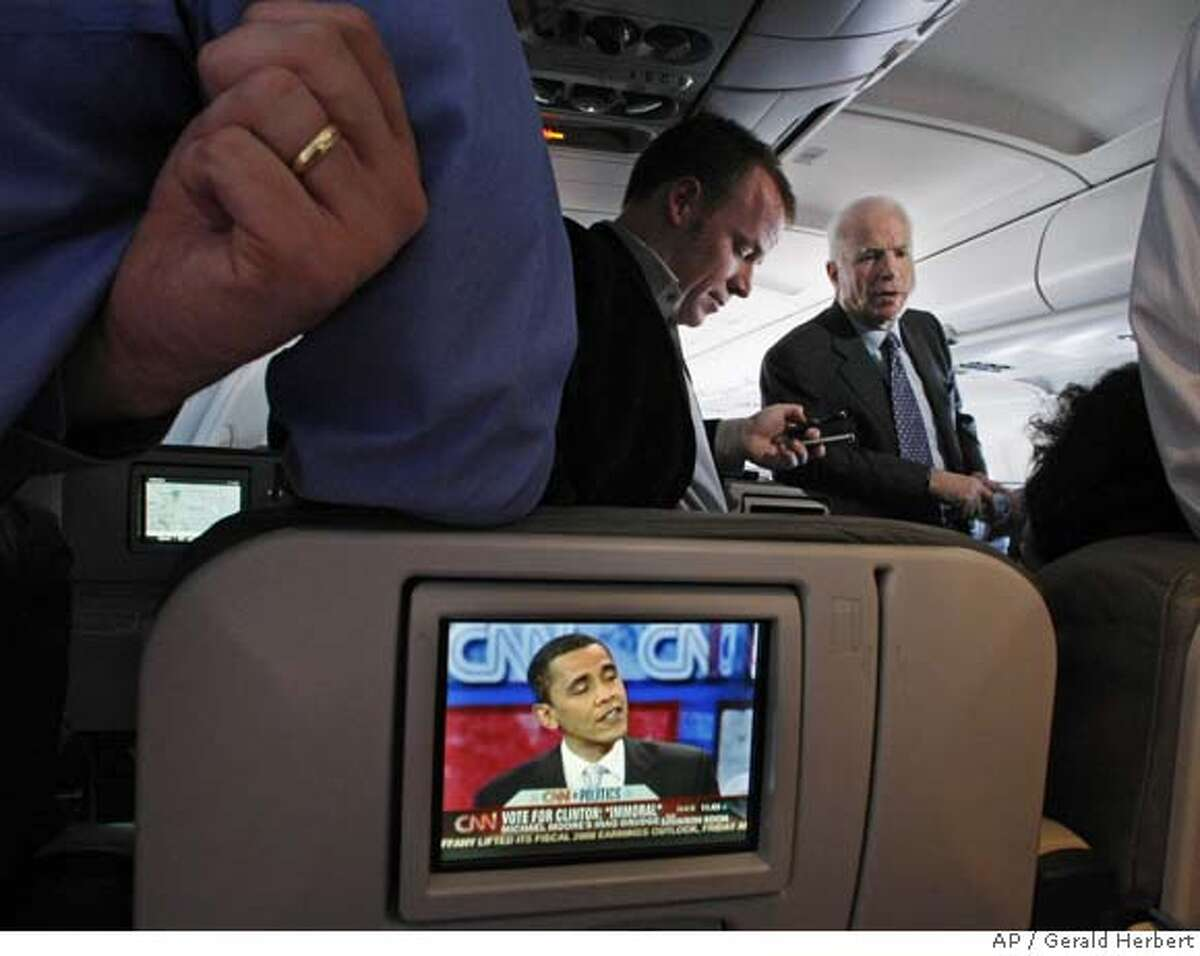 Republican presidential hopeful, Sen. John McCain, R-Ariz., talks with reporters on his campaign plane enroute from Kansas to Seattle, while one of his Democratic rivals, Sen. Barack Obama, D- Ill., is seen on an in flight TV screen Friday, Feb. 8, 2008. (AP Photo/Gerald Herbert)