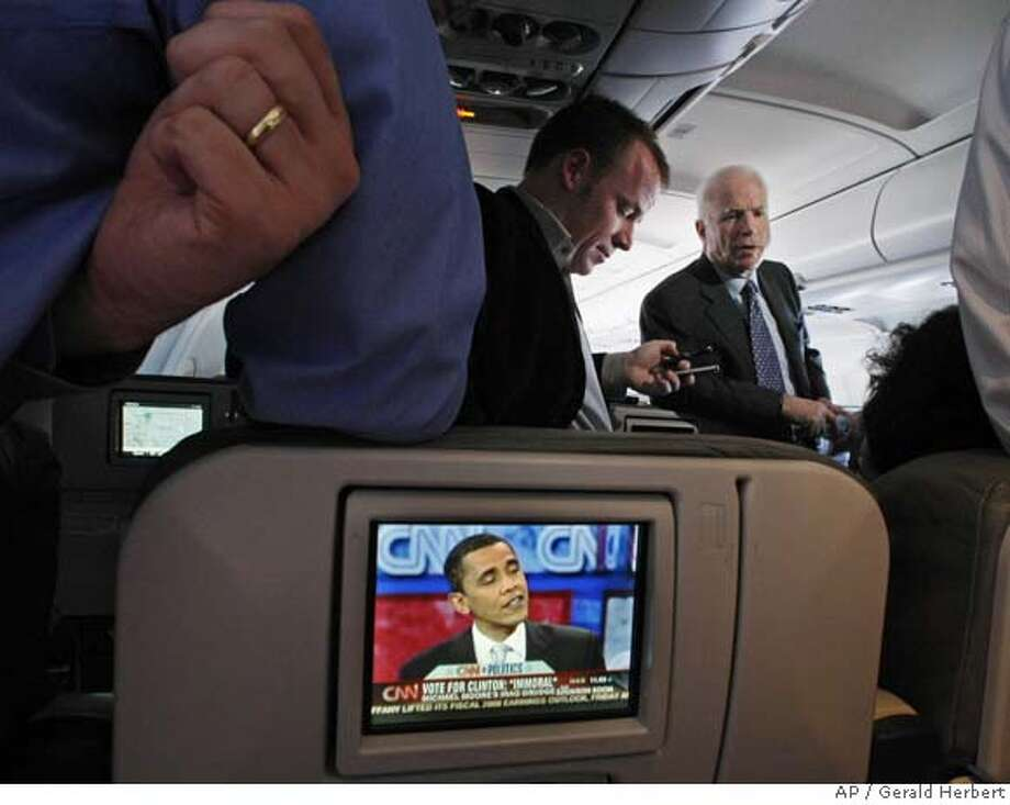 Republican presidential hopeful, Sen. John McCain, R-Ariz., talks with reporters on his campaign plane enroute from Kansas to Seattle, while one of his Democratic rivals, Sen. Barack Obama, D- Ill., is seen on an in flight TV screen Friday, Feb. 8, 2008. (AP Photo/Gerald Herbert) Photo: Gerald Herbert