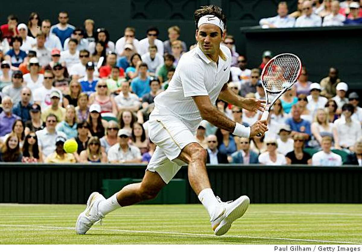 WIMBLEDON, ENGLAND - JUNE 26: Roger Federer of Switzerland plays a backhand during the men's singles third round match against Philipp Kohlschreiber of Germany on Day Five of the Wimbledon Lawn Tennis Championships at the All England Lawn Tennis and Croquet Club on June 26, 2009 in London, England. (Photo by Paul Gilham/Getty Images)
