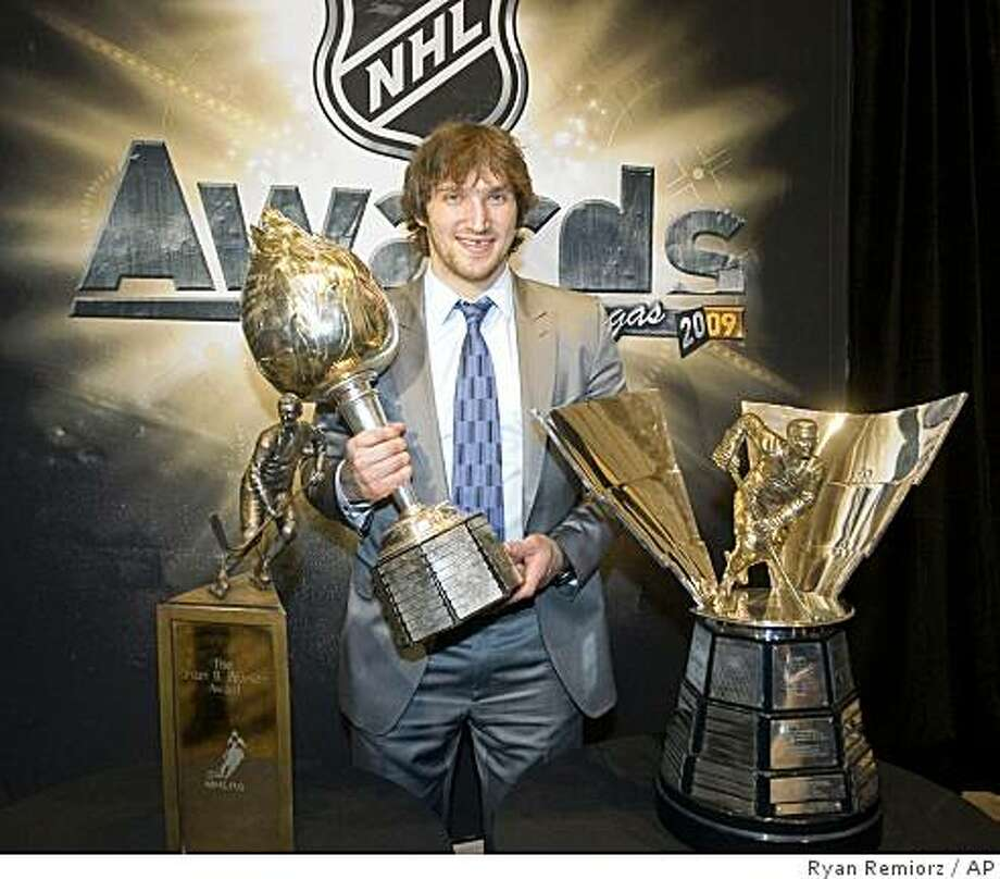 Washington Capitols' Alex Ovechkin, of Russia, holds the Hart Memorial trophy as he poses with Lester Pearson Trophy, left, and the Maurice Richard trophy at the National Hockey League awards in Las Vegas Thursday, June 18, 2009. Ovechkin captured the two most prestigious awards in hockey for the second straight season on Thursday, winning the Hart Trophy as NHL MVP and the Lester B. Pearson Award as the players' choice for the most outstanding player. (AP Photo/The Canadian Press, Ryan Remiorz) Photo: Ryan Remiorz, AP