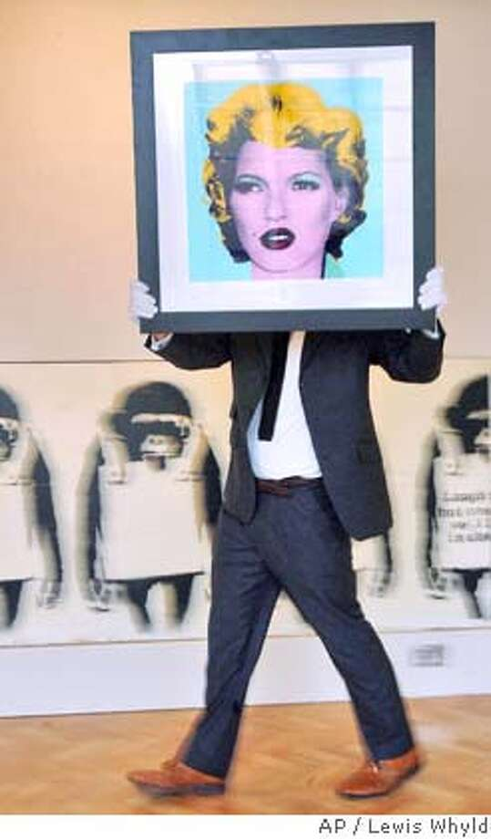 ** FILE ** Urban art specialist Gareth Williams carries Banksy's 'Kate Moss' at Bonhams auction house, London, in this Jan. 22, 2008 file photo. English graffiti artist Banksy's screen print of supermodel Kate Moss sold for 96,000 pounds (euro 130,000, US$191,000) Tuesday, Feb. 5, 2008 at a street art auction in London, the auction house said. (AP Photo/PA, Lewis Whyld, File) ** UNITED KINGDOM OUT, NO SALES, NO ARCHIVE ** Photo: Lewis Whyld