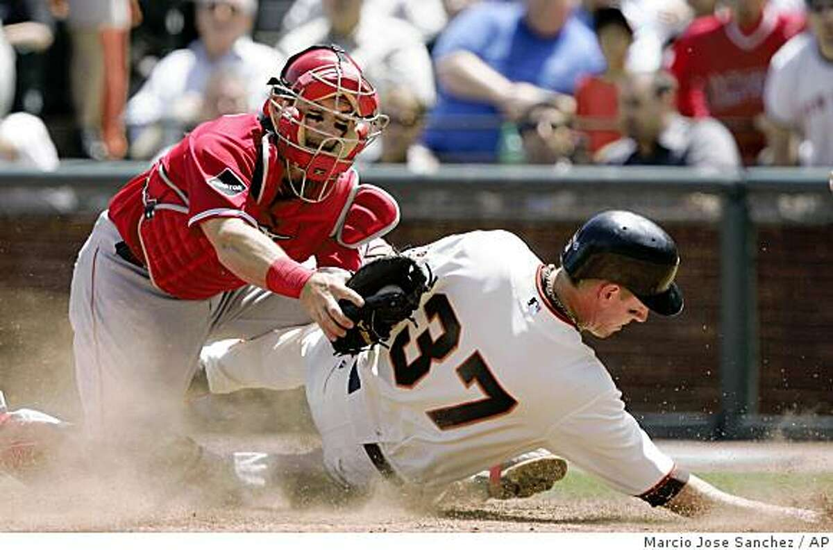 Los Angeles Angels catcher Jeff Mathis, left, collides with San Francisco Giants' Matt Downs (37) at the plate after a single by Giants' Edgar Renteria during the seventh inning of a baseball game in San Francisco, Wednesday, June 17, 2009. Downs was out at the plate. Los Angeles won 4-3. (AP Photo/Marcio Jose Sanchez)