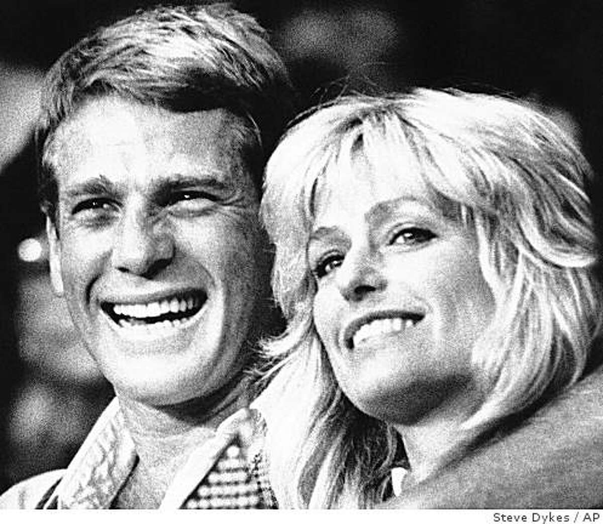 FILE - In this Aug. 12, 1985 file photo, actor Ryan ONeal, left, and actress Farrah Fawcett smile while sitting ringside at the Hollywood Palladium where a trio of U.S. Olympic boxers celebrated the one-year anniversary of their gold medal winning performances in Los Angeles, Calif. Fawcett died Thursday, June 25, 2009 in a Los Angeles hospital. She was 62. (AP Photo/Steve Dykes, file)