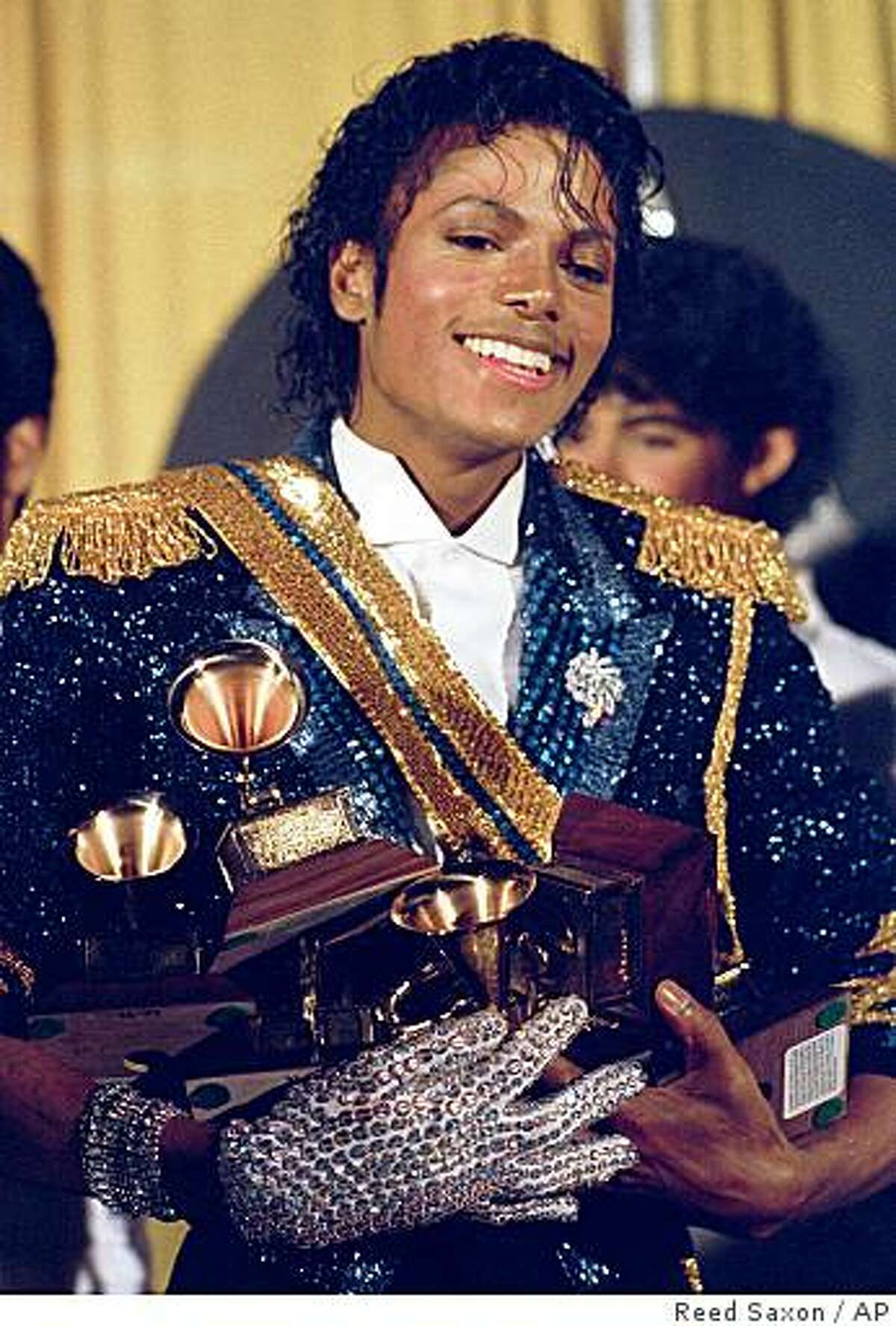 Michael Jackson is seen backstage at the 26th annual Grammy Awards in Los Angeles as he poses with the awards he won in eight different categories on February 28, 1984.