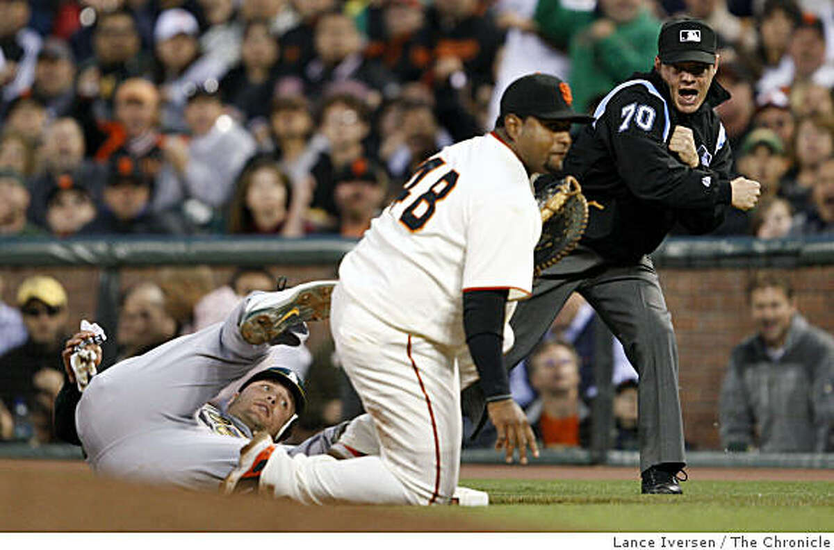Umpire Tim Welke calls out Athletics Matt Holliday at first base after Giants Pablo Sandoval placed the pick-off tag on Holiliday in the 6th inning at AT&T Park in San Francisco on Saturday.