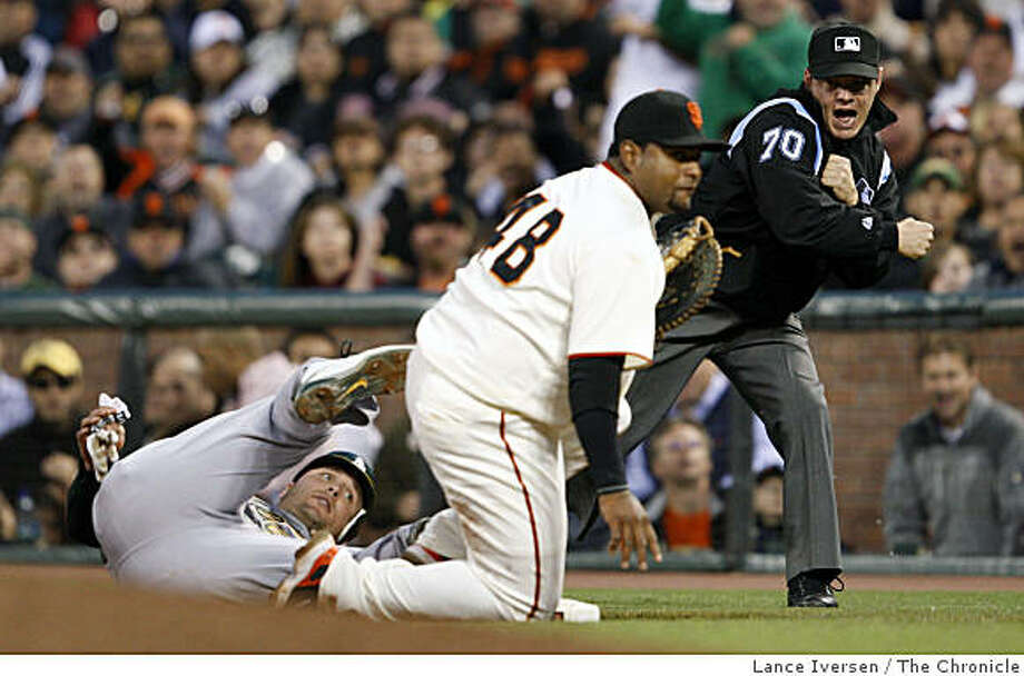 Umpire Tim Welke calls out Athletics Matt Holliday at first base after Giants Pablo Sandoval placed the pick-off tag on Holiliday in the 6th inning at AT&T Park in San Francisco on Saturday. Photo: Lance Iversen, The Chronicle