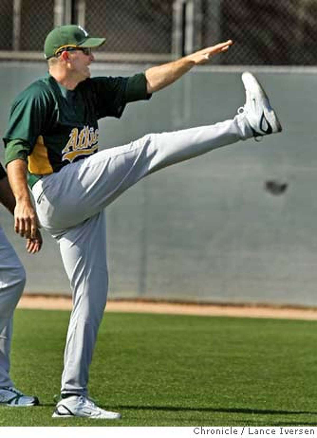 A's first baseman Mike Sweeney stretches during his daily morning workout. Pitchers and catchers warm up on the infield at Papago Park, home of the Oakland Athletics for spring training in Phoenix, Saturday morning. By Lance Iversen/The San Francisco Chronicle MANDATORY CREDIT PHOTOG AND SAN FRANCISCO CHRONICLE/NO SALES MAGS OUT