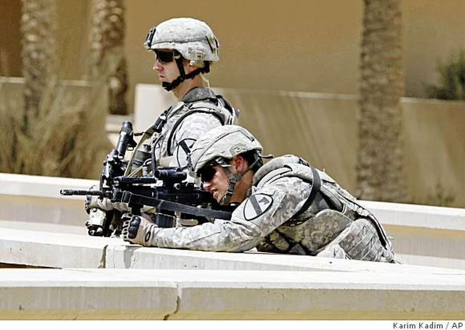 ** CORRECTS THE FACT BAGHDAD ISLAND WAS BASED ON A DESIGN BY FRANK LLOYD WRIGHT  ** U.S. Army soldiers provide security at a groundbreaking ceremony for the revitalization of Baghdad Island, built in the 1980s and based on a design by Frank Lloyd Wright in Baghdad, Iraq, Monday, June 22, 2009. U.S. and Iraqi officials have begun renovating an amusement park on an island north of Baghdad. It's the latest effort to restore a sense of normalcy amid security gains and reflects a U.S. focus on civil affairs projects ahead of next week's deadline for combat troops to withdraw from cities. The 150-acre Tigris River complex was a popular site for weddings and other celebrations before the U.S.-led invasion in March 2003. But it was devastated by looting in the aftermath. (AP Photo/Karim Kadim) Photo: Karim Kadim, AP