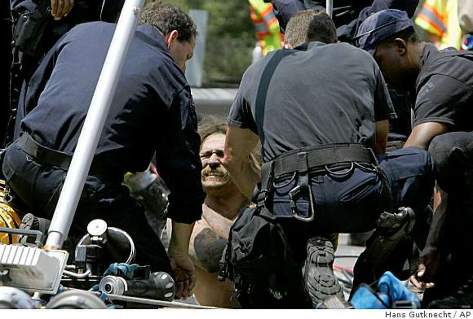 Los Angeles Police SWAT officers take a suspect into custody after he was holed up for hours in a storm drain under a busy freeway in Los Angeles, Calif. Tuesday, June 16, 2009. The incident began with a report that someone was trying to steal copper wire in the area. (AP Photo/LA Daily News, Hans Gutknecht)  ** LA TIMES OUT, VENTURA STAR OUT, AV PRESS OUT, NEWHALL SIGNAL OUT, MAGS OUT, ONLINE OUT, SALES OUT  ** Photo: Hans Gutknecht, AP