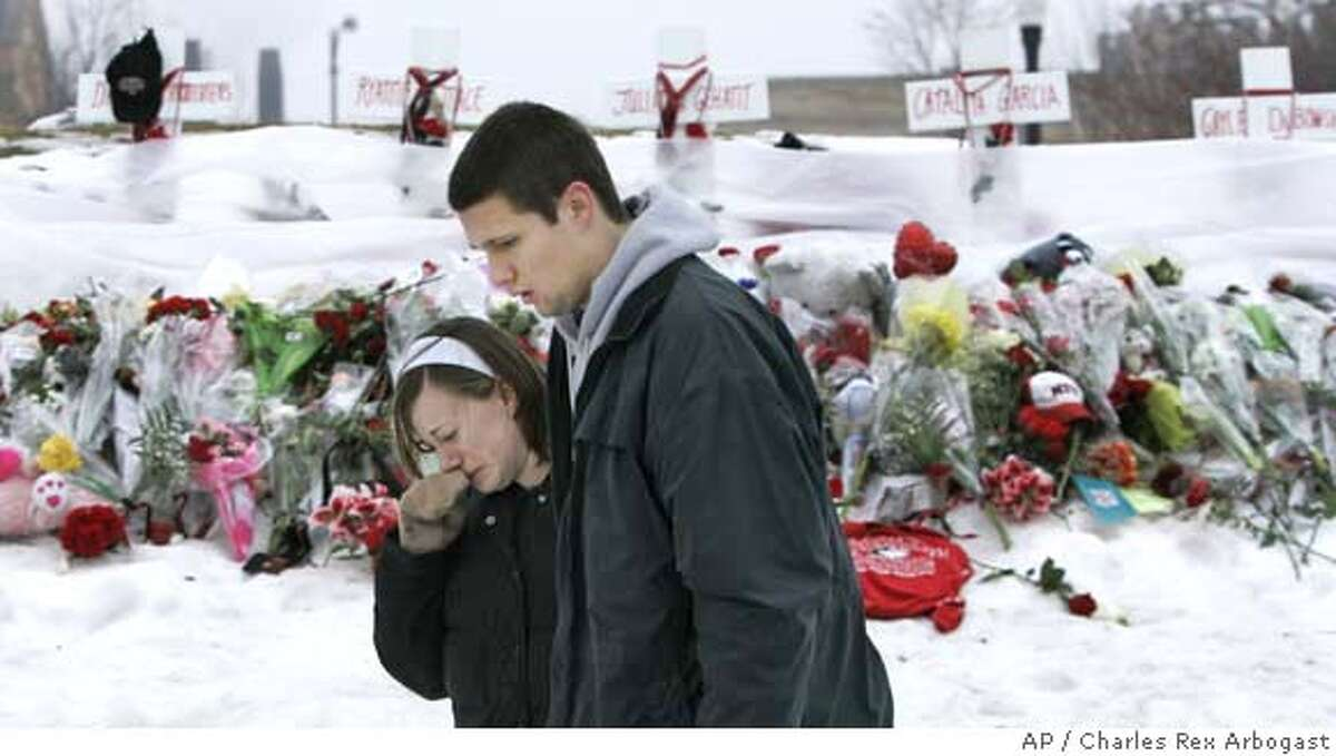 Mourners at Northern Illinois University console each other after placing flowers at a memorial for the five victims of the Valentines Day shooting on the campus of NIU in DeKalb, Ill., Sunday, Feb. 17, 2008. (AP Photo/Charles Rex Arbogast)