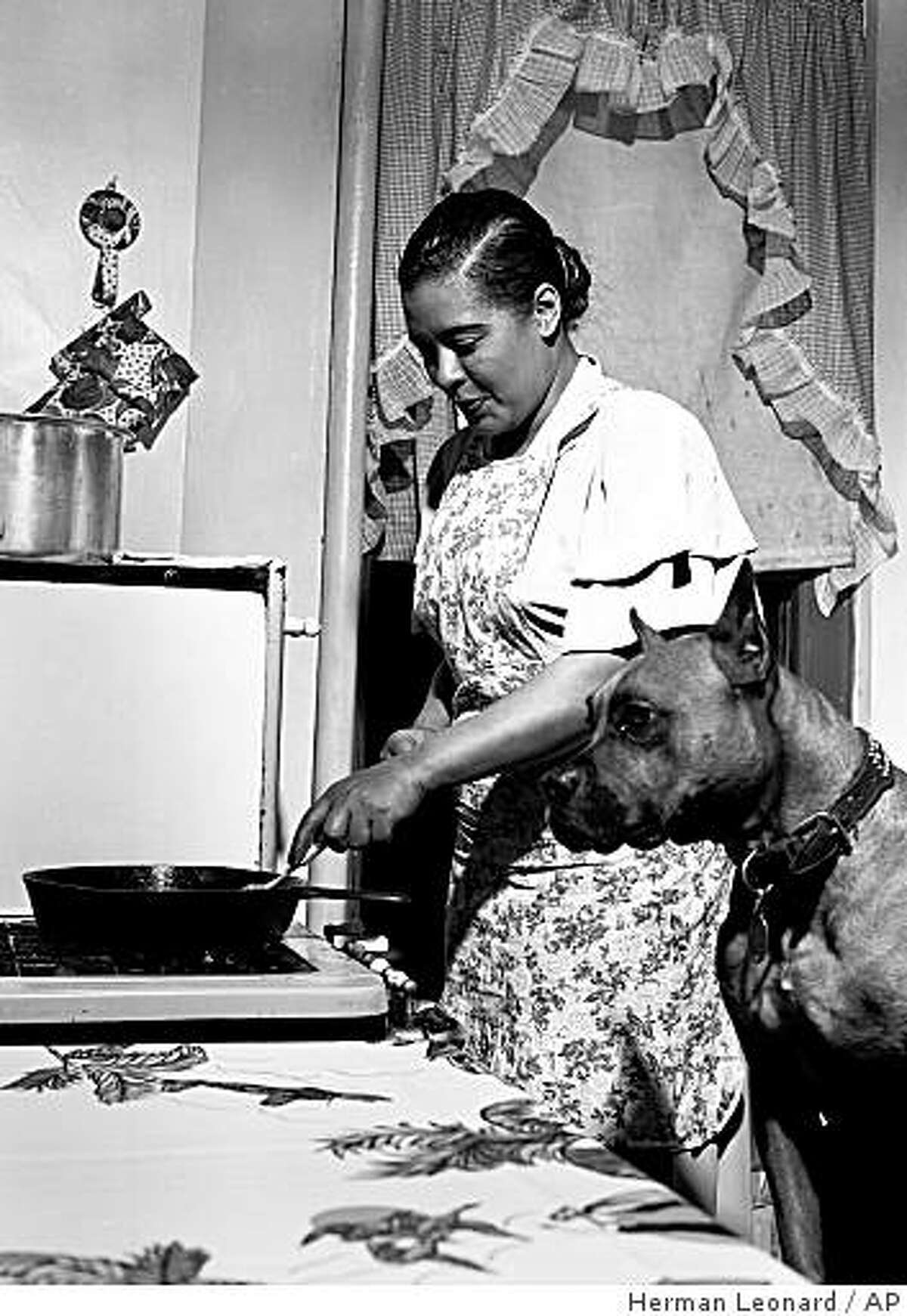 This 1949 photo released by Herman Leonard Photography, shows Billie Holiday cooking a steak for her dog Mister in her apartment in the Harlem neighborhood of New York. The photographer, Herman Leonard, said she came to the door wearing a simple house dress and an apron and