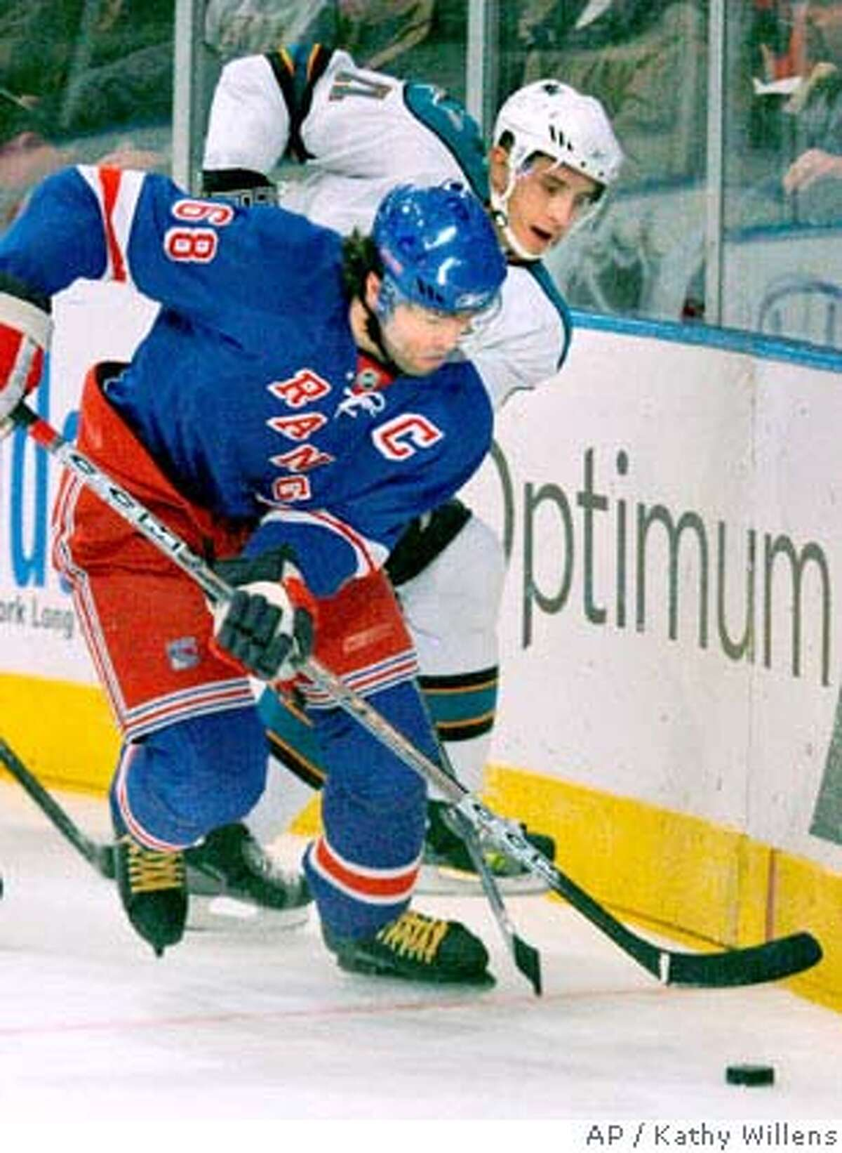 New York Rangers right wing Jaromir Jagr (68), of the Czech Republic, and San Jose Sharks defenseman Alexei Semenov (21), of Russia, battle for the puck behind the net at Madison Square Garden in New York, Sunday, Feb. 17, 2008. (AP Photo/Kathy Willens)