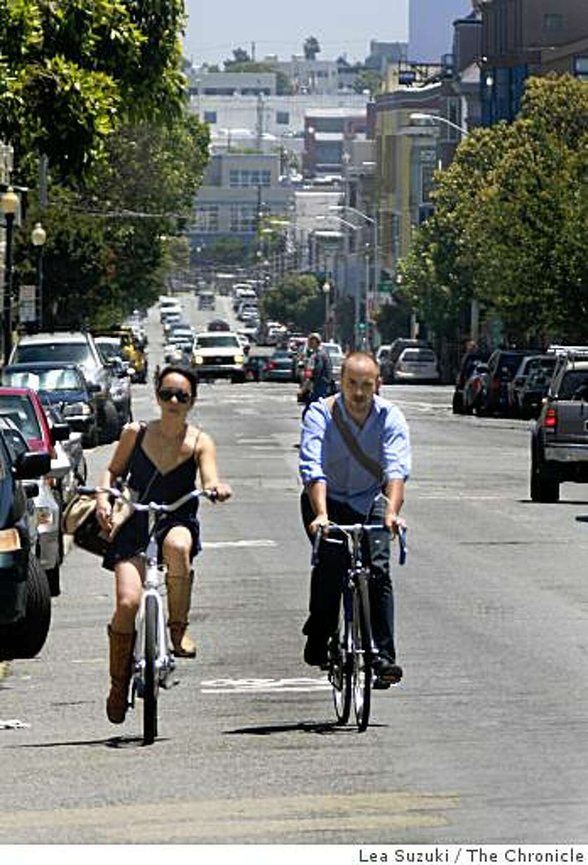 Monika Collins and Stephen Osadetz, both of San Francisco, chat as they pedal their bikes on 17th street near Dolores street on Tuesday June 23, 2009 in San Francisco, Calif.