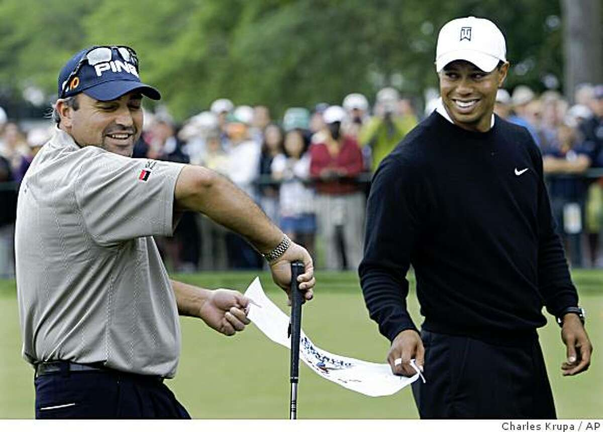 Angel Cabrera, left, of Argentina shows off his sleeve after getting Tiger Woods to sign a flag for him during their practice session for the U.S. Open Golf Championship at Bethpage State Park's Black Course in Farmingdale, N.Y., Tuesday, June 16, 2009. (AP Photo/Charles Krupa)