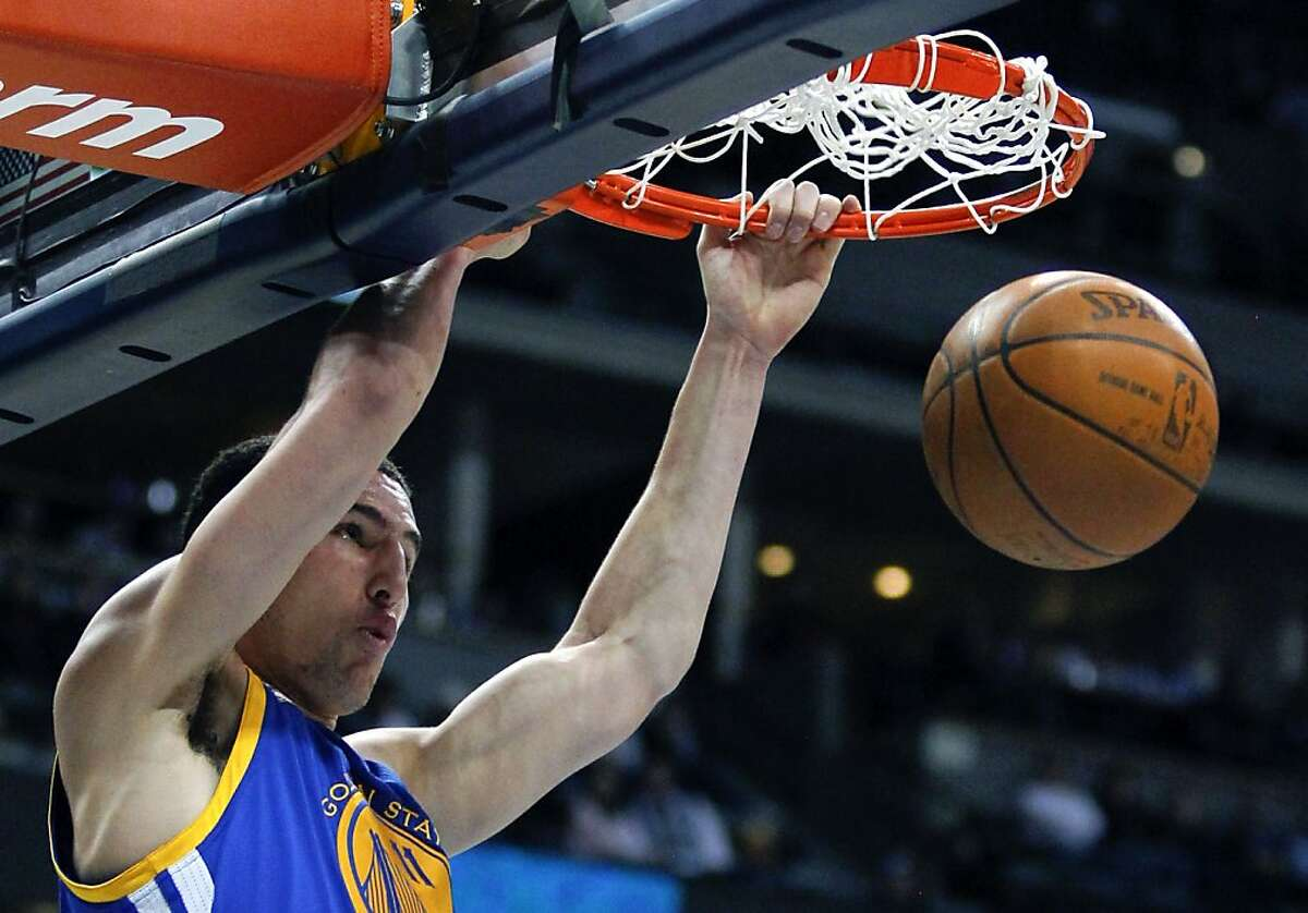 Golden State Warriors guard Klay Thompson (11) dunks against the Denver Nuggets during the fourth quarter of an NBA basketball game Thursday, Feb. 9, 2012 in Denver. The Warriors won 109-101. (AP Photo/Barry Gutierrez)