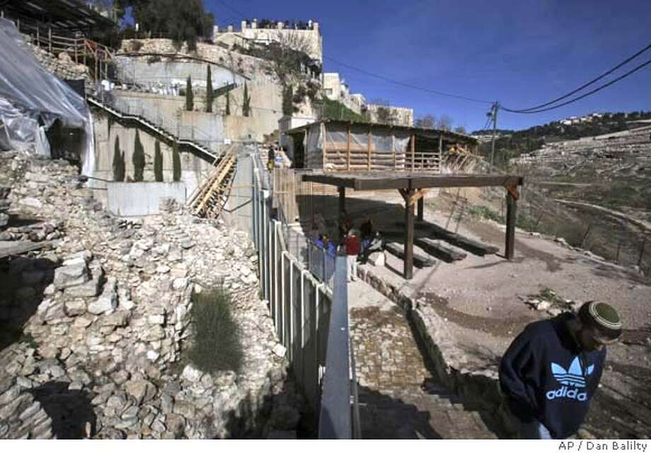 A tourist walks outside at the City of David, near Jerusalem's Old City, Monday, Dec. 31, 2007. Underneath the homes and ragged streets of the Palestinian neighborhood of Silwan lie the buried remnants of a glorious Jewish past: a subterranean water tunnel hewed by a Judean king 2,700 years ago, a road that once led to a biblical Temple, and coins, seals and other detritus of Jerusalem's turbulent history.(AP Photo/Dan Balilty) A DEC. 31, 2007 PHOTO Photo: DAN BALILTY