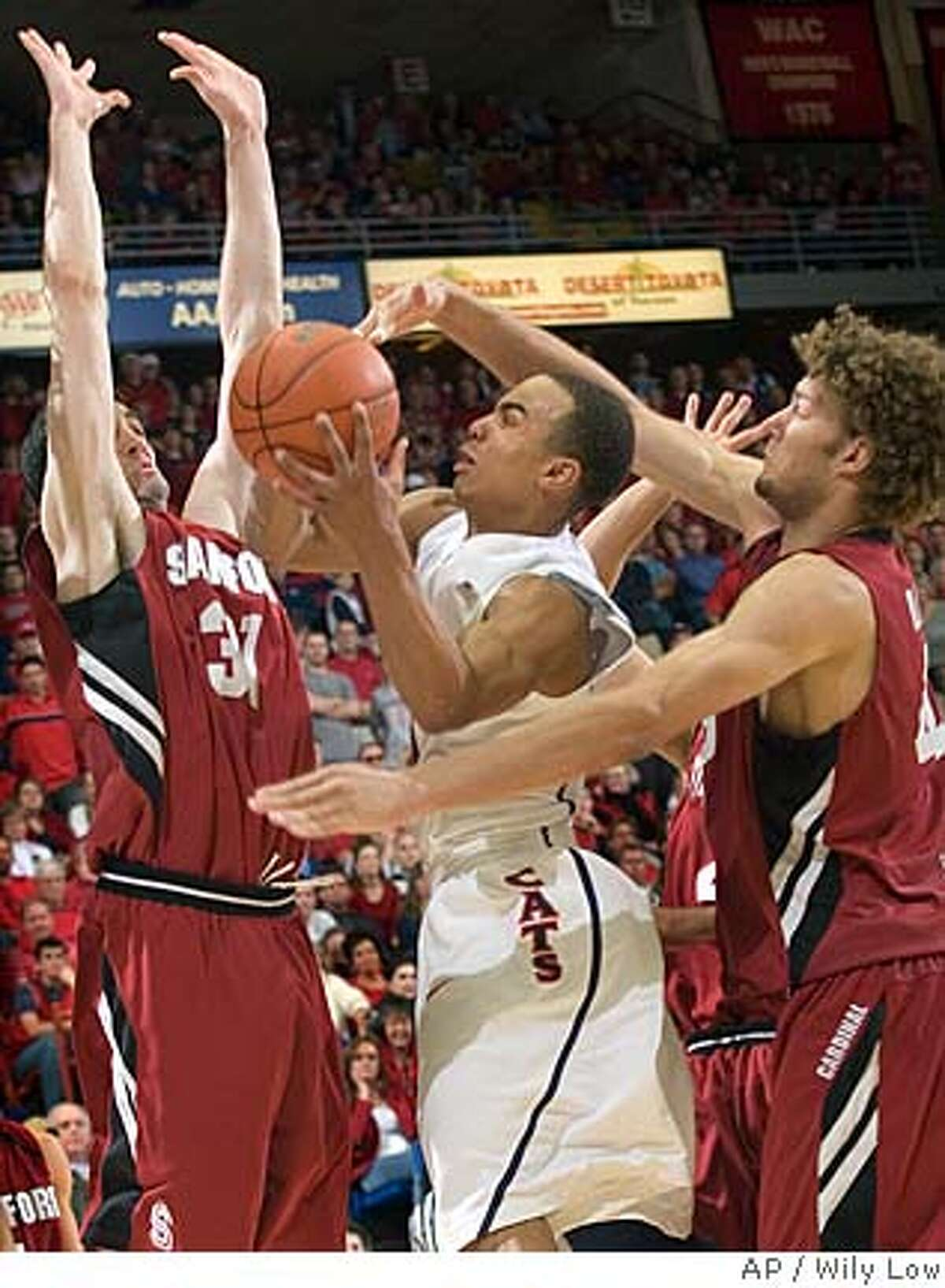 Arizona's Jerryd Bayless, middle, tries to shoot between Stanford's Robin Lopez, right, and Taj Finger (31) in the second half of a college basketball game at McKale Center in Tucson, Ariz., Saturday, Feb. 16, 2008. Stanford won, 67-66. (AP Photo/Wily Low)