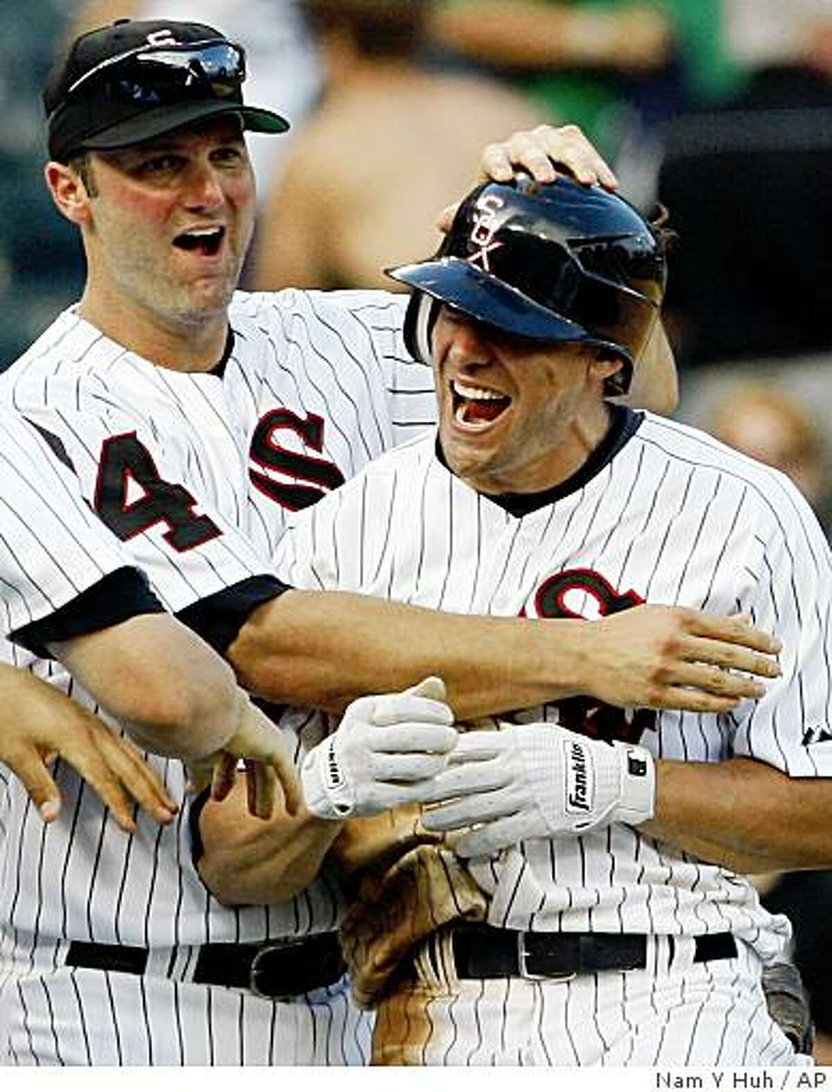 Chicago White Sox's Scott Podsednik, right, celebrates with Paul Konerko after Podsednik drove in the winning run against the Los Angeles Dodgers during the 13th inning of an interleague baseball game in Chicago, Thursday, June 25, 2009. The White Sox won 6-5. (AP Photo/Nam Y. Huh)